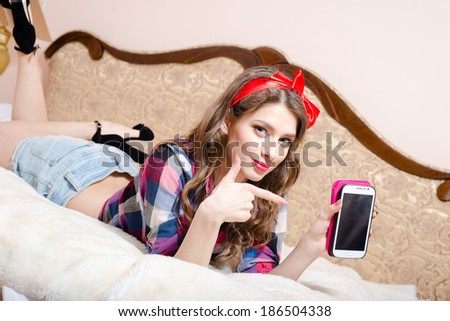 beautiful attractive young woman pinup girl relaxing lying in bed with finger showing or pointing at mobile phone happy smiling & looking at camera - stock photo