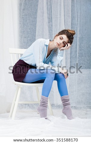 Beautiful attractive young woman sitting on chair posing in studio.