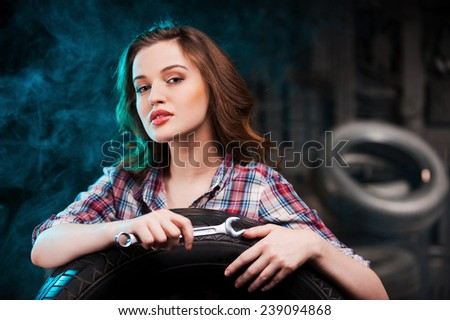 Beautiful auto mechanic. Beautiful young woman holding work tool and looking at camera while leaning at the car tire in auto repair shop - stock photo