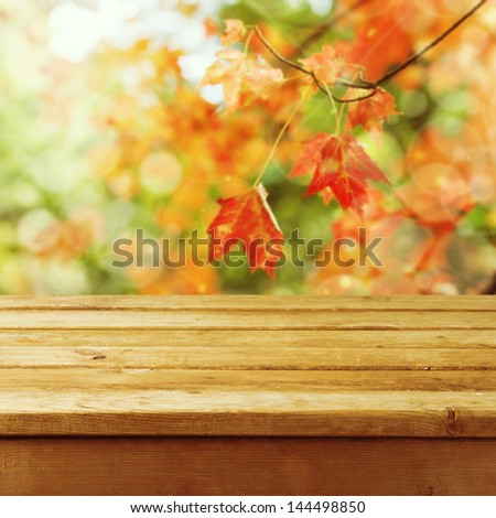 Beautiful autumn background with empty wooden deck table. Ready for product montage display. - stock photo