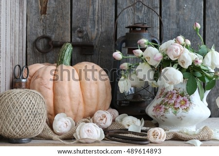 "Beautiful autumn composition with pumpkin ""Porcelain dolly"", fresh white roses in vintage, antique porcelain pitcher, vase, wooden spool with rustic scissors, big old key, old oil lamp, lantern, jute"