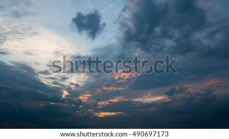 Beautiful autumn evening building clouds with sunset close to night. Clear crisp cloudscape with large, building clouds and light rays, perfect for digital composition background.