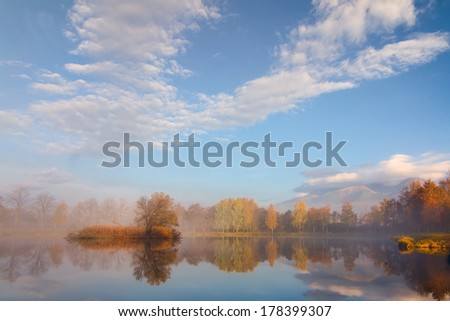 Beautiful Autumn Fall landscape over foggy misty lake