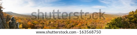 Beautiful autumn forest panoramic view with village in the distance - stock photo