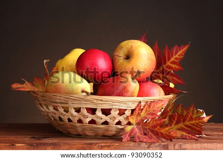 beautiful autumn harvest in basket and leaves on brown background