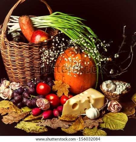 Beautiful autumn harvest of vegetables and leaves on black background  - stock photo