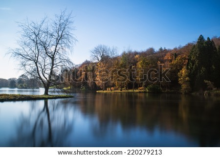 Beautiful Autumn lake landscape with vibrant colors reflected in still waters