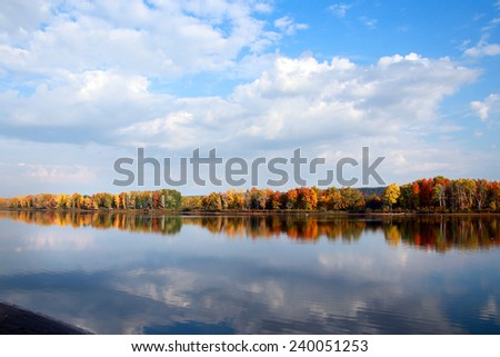 beautiful autumn landscape forest with colorful leaves and mirror-like surface of the river on a warm sunny day