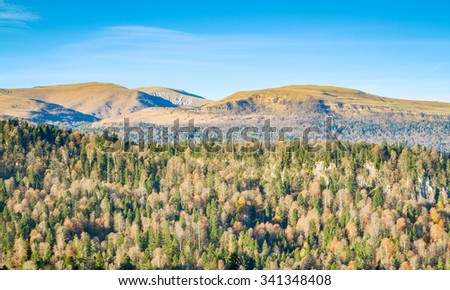 Beautiful autumn landscape. Mountains forest meadows. Panoramic view.