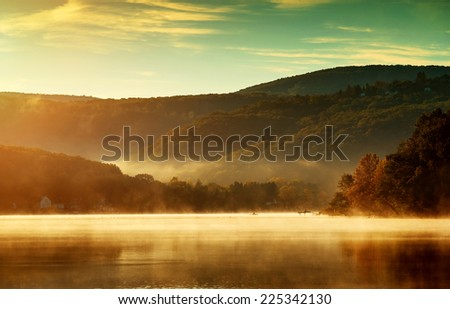 Beautiful autumn landscape, the lake in the morning fog  - stock photo