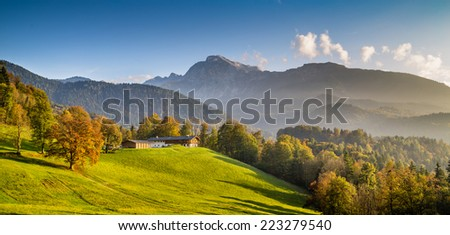 Beautiful autumn landscape with traditional farm house in the Alps in golden evening light - stock photo