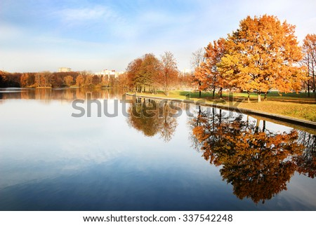 Beautiful autumn park.  Mirror reflection of trees in water. Autumn
