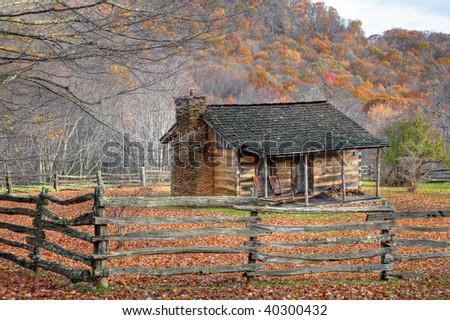 Beautiful Autumn scene showing rustic old log cabin surrounded by split rail fence