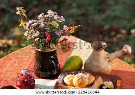 Beautiful autumn still life composition with bright bouquet of natural flowers, coffee, cherry jam, green pear, chocolate candies and profiteroles outdoors