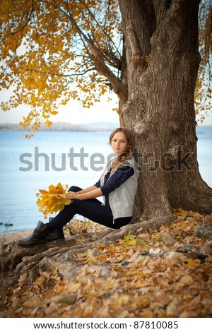 Beautiful autumn tree on the coast of the river and the young woman.