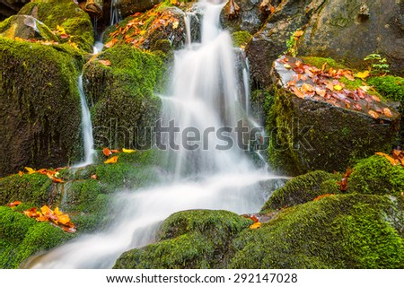 Beautiful autumn waterfall with golden foliage and silver streams of water - stock photo