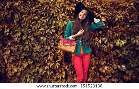 Beautiful autumn woman holding handbag wearing black hat against leaves  - stock photo