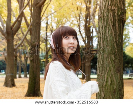 Beautiful autumn woman listening to music in autumn