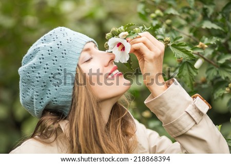 Beautiful autumn woman smell last autumn flower. selective focus on lips and pistil - stock photo