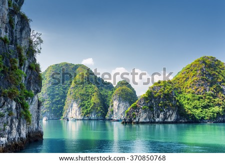 Beautiful azure water of lagoon in the Halong Bay (Descending Dragon Bay) at the Gulf of Tonkin of the South China Sea, Vietnam. Scenic landscape formed by karst towers-isles on blue sky background. - stock photo
