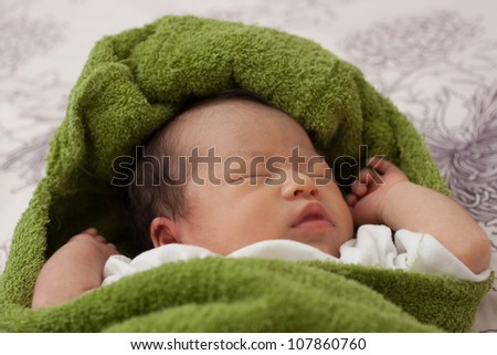 Beautiful Baby Asian Infant Girl covered in green blanket - stock photo