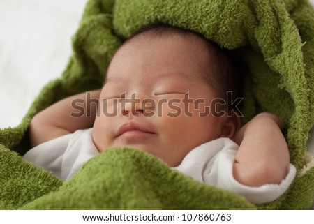 Beautiful Baby Asian Infant Girl covered in green blanket