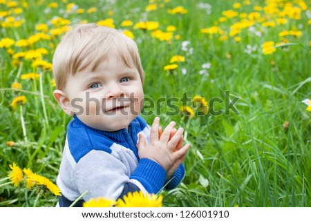 Beautiful baby boy in yellow flowers field summer