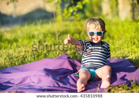 beautiful baby child in sunglasses gesture class outside - stock photo