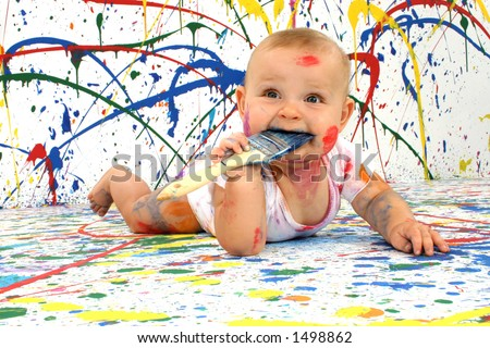 Beautiful baby covered in bright paint with paint brush in mouth.