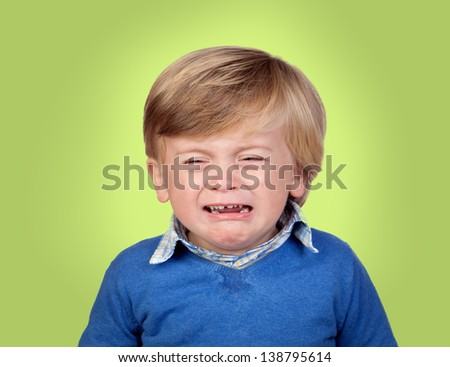 Beautiful baby crying isolated on green background - stock photo