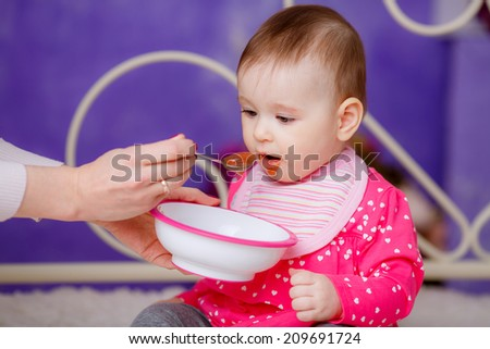 beautiful baby eating baby food - stock photo