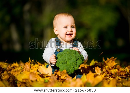 Beautiful baby girl eating food outdoor in nature