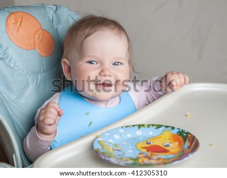 Beautiful baby girl eating mashed. Child itself with a spoon