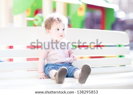 Beautiful baby girl enjoying the sun on a playground
