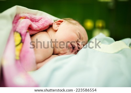 Beautiful baby girl few minutes after the birth lying on her mother, skin to skin contact - stock photo