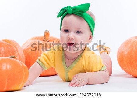 beautiful baby girl in a yellow body with green bow on her head lying on his stomach on a white background including pumpkins, picture with depth of field