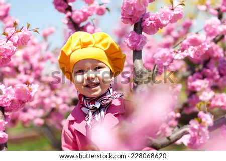 Beautiful baby girl in blooming apricot tree branches. - stock photo
