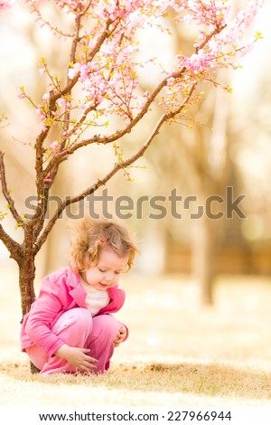 Beautiful baby girl in blooming jasmin tree branches. - stock photo