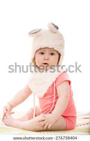 Beautiful baby girl in fluffy bunny hat  sitting on blanket - stock photo