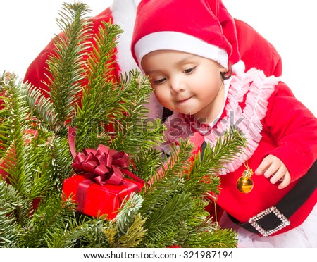 Beautiful baby girl in front of the christmas tree - stock photo