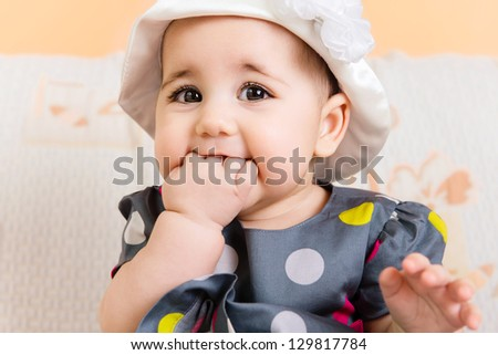 Beautiful baby girl in hat and dress portrait - stock photo