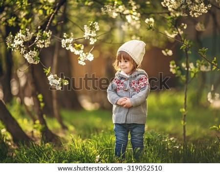 Beautiful baby girl in spring garden - stock photo