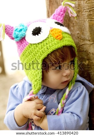 Beautiful baby girl is in the little cap of owl - stock photo