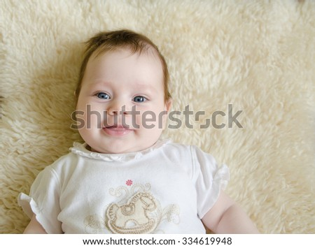 beautiful baby girl laying on a fur rug with a sweet expression on her face - stock photo