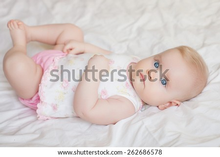 beautiful baby girl lying on white bed - stock photo