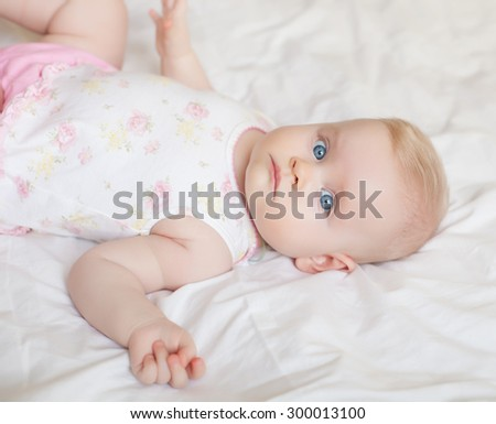 beautiful baby girl lying on white bed