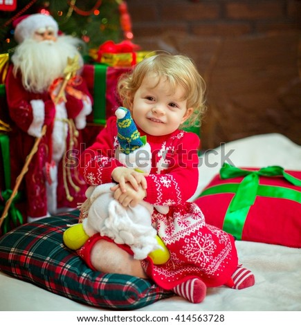 Beautiful baby girl near a Christmas tree with gifts