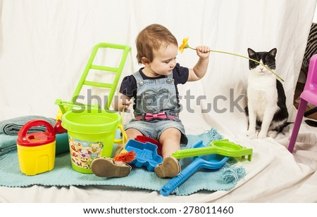 Beautiful baby girl play in studio with a black and white cat