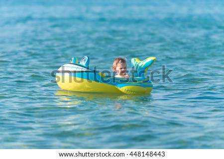 Beautiful baby girl playing in a inflatable boat at the beach