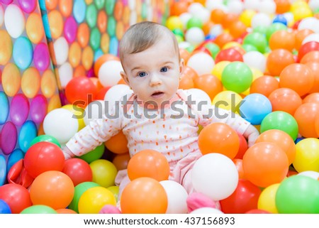 Beautiful baby girl playing with colorful balls